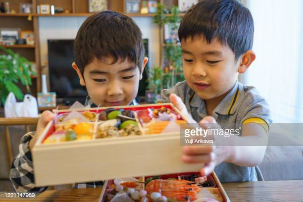 two boys looking at osechi, japanese traditional new years dish - 6 7 years stock pictures, royalty-free photos & images