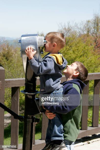 Two boys looking through a telescopic viewer at Skyland Resort.