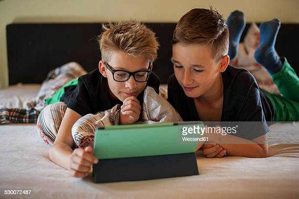 Two boys lying on bed using digital tablet