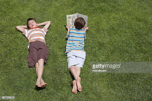 Two boys (6-11) lying on grass one reading elevated view