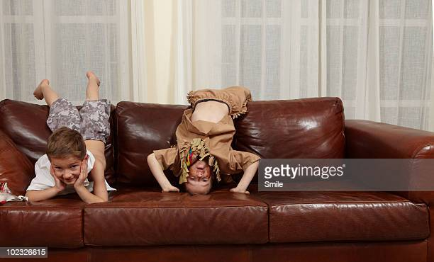Two boys lying over the back of couch