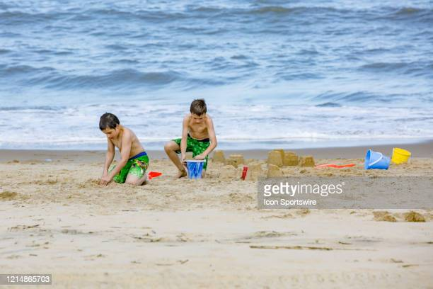 Two boys make sand castles on Memorial Day weekend on May 22 in Virginia Beach VA This is the first day of the beach's reopening for swimming...