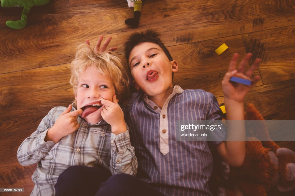 Two boys making funny faces while playing on the floor : Stock Photo