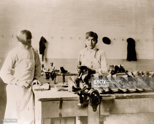 Two boys making or repairing shoes at Carlisle Indian School] 1904
