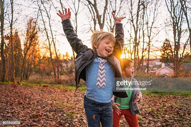 Two boys messing about with autumn leaves