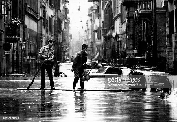 Two boys move along a street turned into a canal by the flood riding a sort of raft makeshift boat Florence 1966