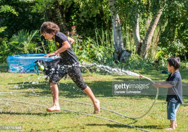 two boys of 4 years old and 12 years old playing with a hose in the garden - 12 13 years stock pictures, royalty-free photos & images