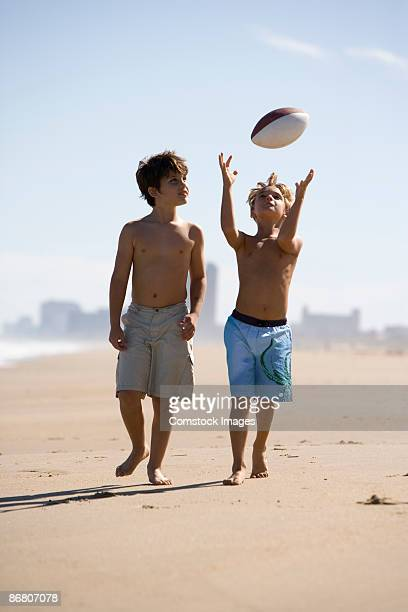 Two boys on a beach throwing a ball