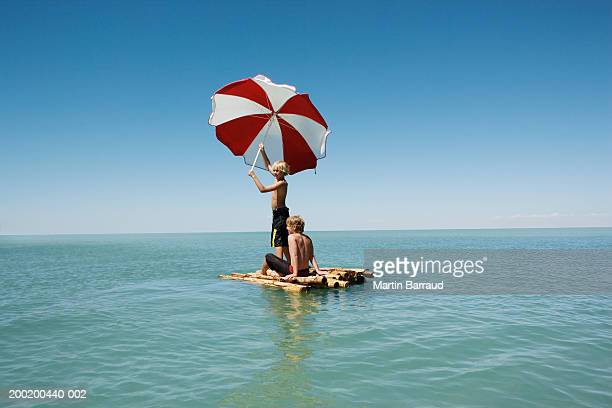 Two boys (10-12) on bamboo raft in sea, one holding up parasol
