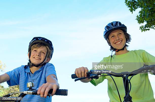 Two boys (11-13) on bicycles wearing cycle helmets, low angle view