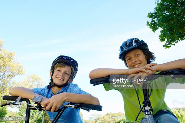 two boys (11-13) on bicycles wearing cycle helmets, smiling, portrait - 10 11 ans photos et images de collection