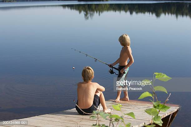 Two boys (10-12) on dock fishing, rear view