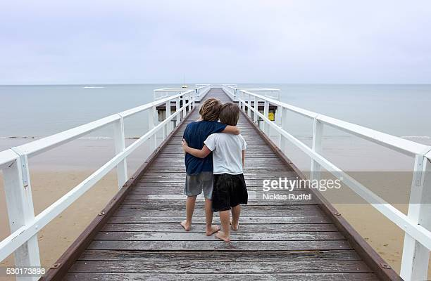 two boys on jetty, arlie beach, australia - permanente - fotografias e filmes do acervo