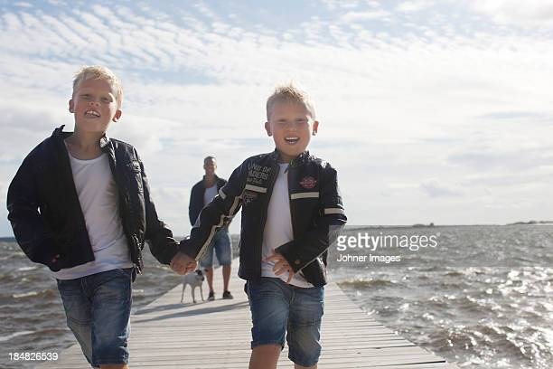 Two boys on jetty, father in background