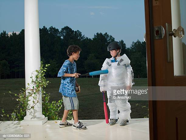 Two boys (10-11) on porch, one wrapped in bubble wrap, other aiming with baseball bat