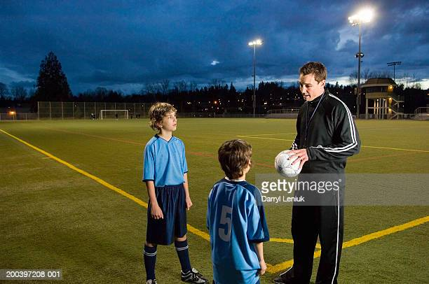 Two boys (8-11) on soccer field with coach, night