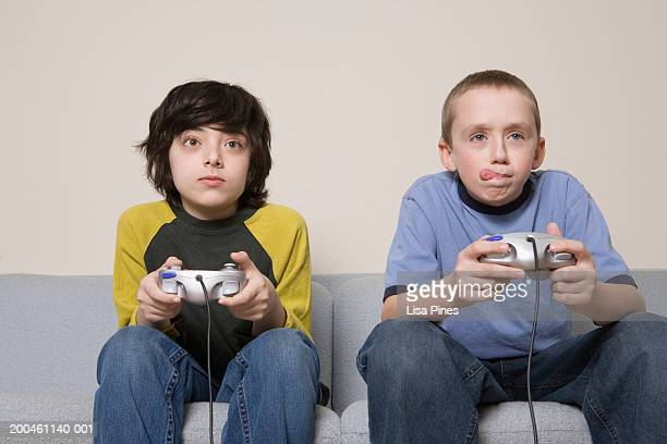 Two boys (11-13) on sofa playing video game