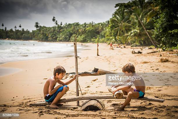 Two Boys on swing made of a log