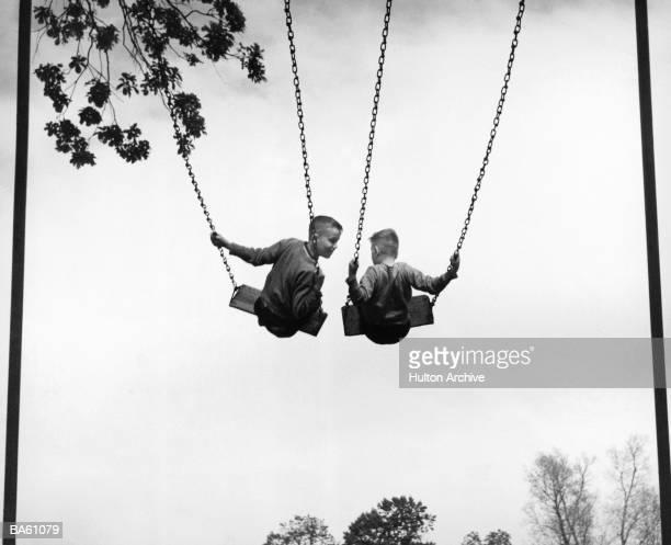 Two boys (6-8) on swings, rear view (B&W)