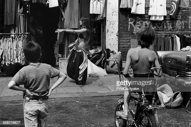 Two boys one on a Chopper watch a woman belly dancing Portobello Road market London August 1975