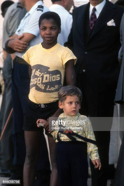 Two boys, one very young, hold hands as they stand with others outside the Nampula Airport during the Mozambican War of Independence, Nampula, Cabo...