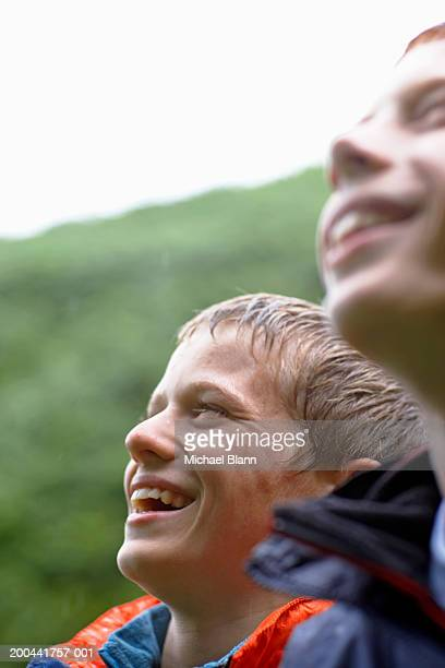 Two boys (11-13) outdoors in rain, smiling, close-up
