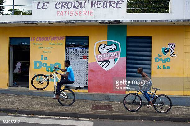 Two boys pass in front of a store depicting the main beer brassed on the Réunion island SaintDenis La Réunion France
