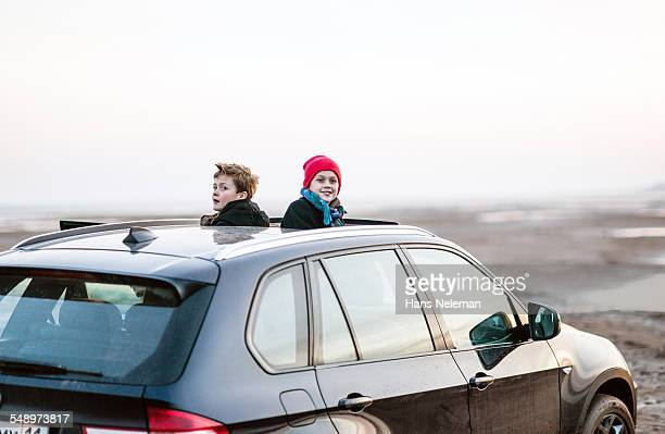 Two boys peeking out of sunroof of car
