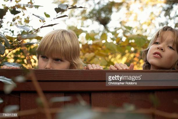 Two boys (10-11) peeping over fence