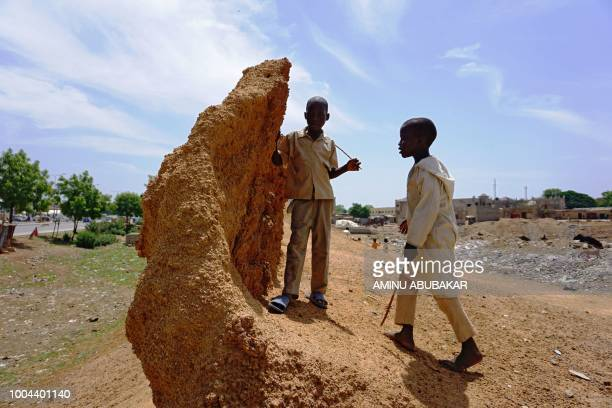 Two boys play at a crumbling section of Kano's ancient wall in Kano Nigeria on June 12 2018 The remnants of these 11th century ramparts are more than...