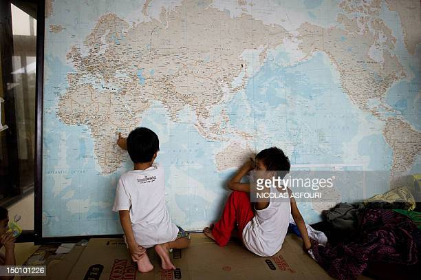 Two boys play with a world map at an evacuation centre at a municipal building in the township of Paombong on the outskirts of Manila on August 10...