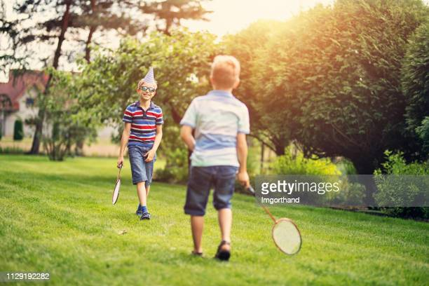 two boys playing badminton in the backyard - racket sport stock pictures, royalty-free photos & images