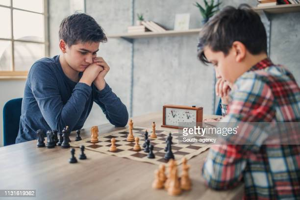 two boys playing chess - chess stock pictures, royalty-free photos & images