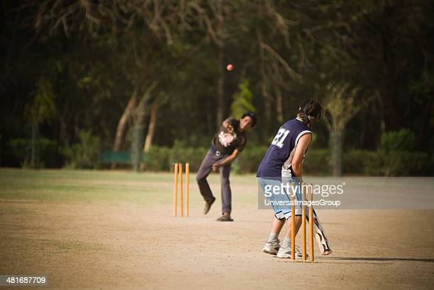 Two boys playing cricket in a playground New Delhi India