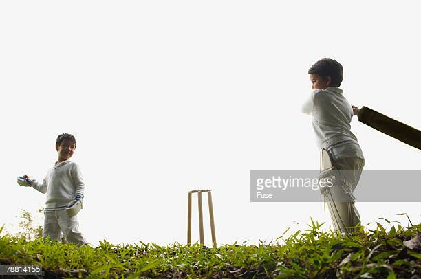 Two Boys Playing Cricket