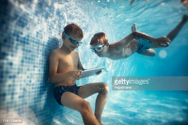two boys playing digital tablet underwater - kids pool games stock pictures, royalty-free photos & images