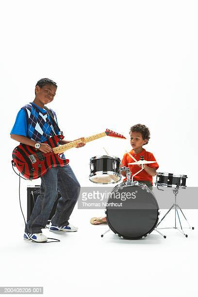 Two boys (5-10) playing electric guitar and drums