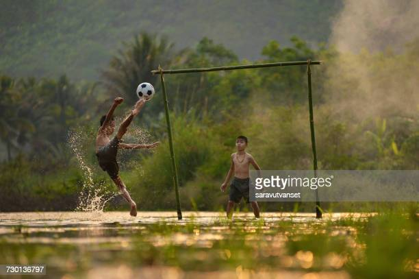 Two boys playing football in a waterlogged field, Thailand