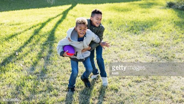 two boys playing football in back yard - naughty america stock pictures, royalty-free photos & images
