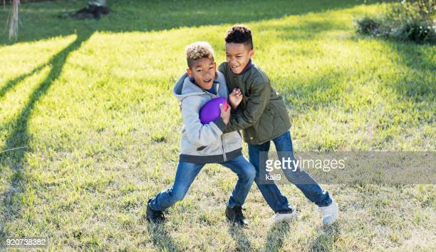 two boys playing football in back yard - mixed wrestling stock pictures, royalty-free photos & images