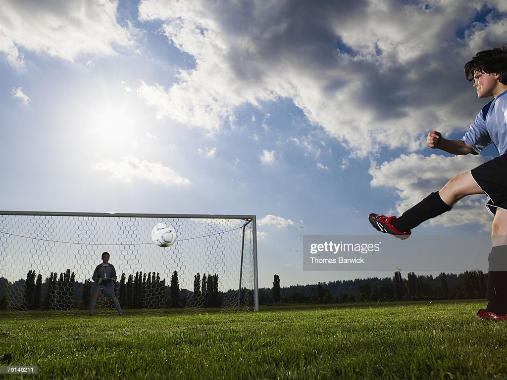 Two boys (10-13) playing football, one kicking, other in goal : Stock Photo