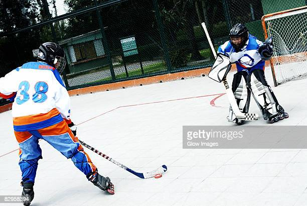 Two boys playing ice hockey