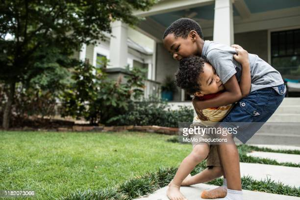 two boys (3 yrs and 6 yrs) playing in front of house - mixed wrestling stock pictures, royalty-free photos & images