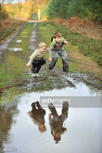 Two boys playing in muddy puddle