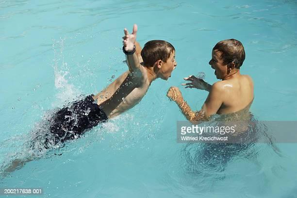 two boys (10-12) playing in pool - jungen in badehose 12 jahre stock-fotos und bilder