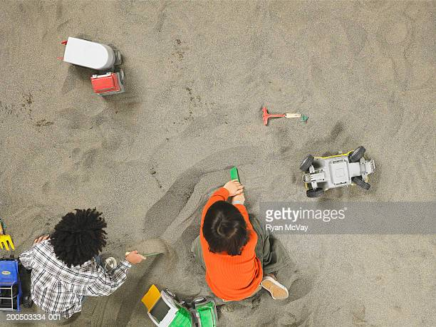 Two boys (5-7) playing in sandbox, overhead view