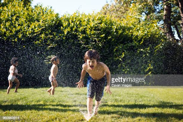 Two boys playing in sprinkler