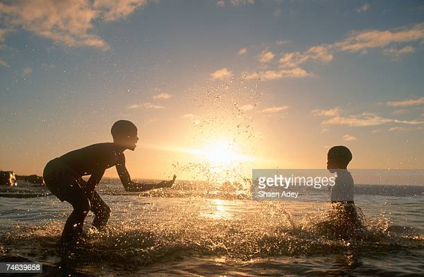 Two Boys Playing in Surf, Silhouetted at Dusk