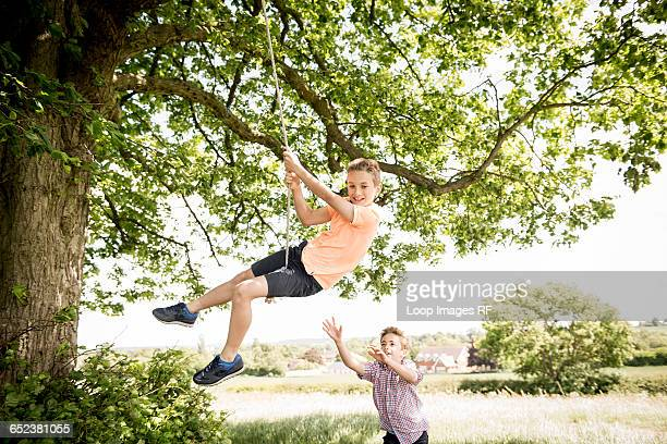 Two boys playing on a swing in the countryside
