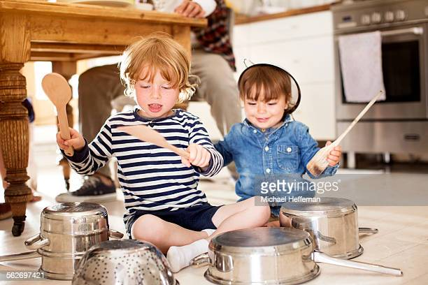Two boys playing on floor with pots and pans
